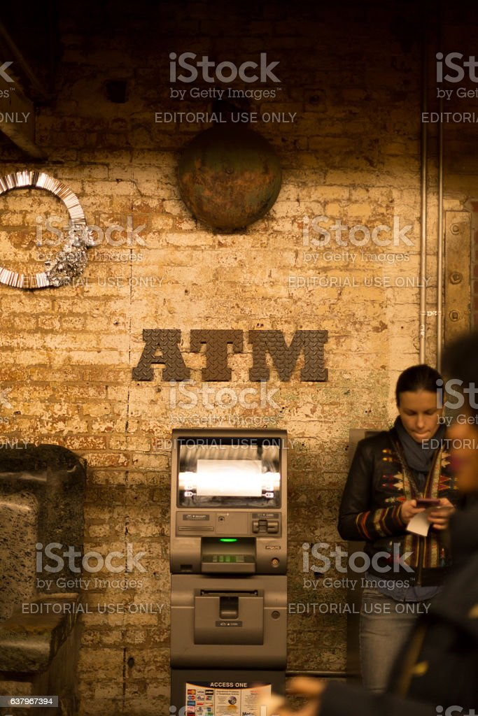 Woman using cell phone next to atm machine stock photo