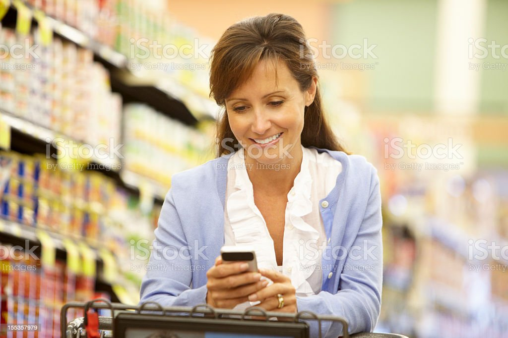 Woman using cellphone in supermarket royalty-free stock photo