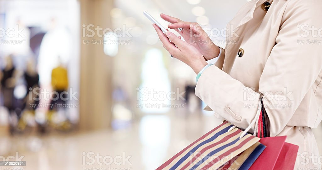 woman using cellphone while shopping stock photo