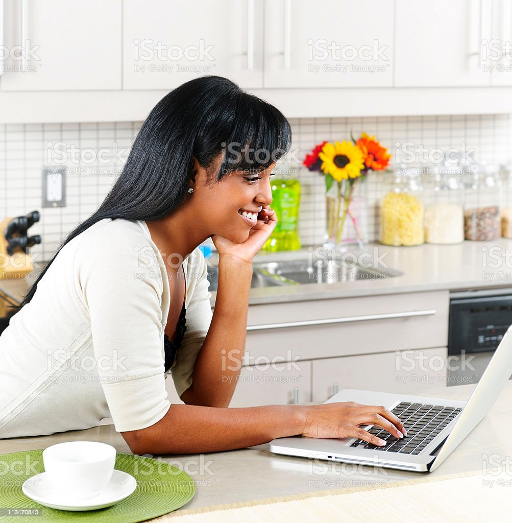 Woman using computer in kitchen royalty-free stock photo