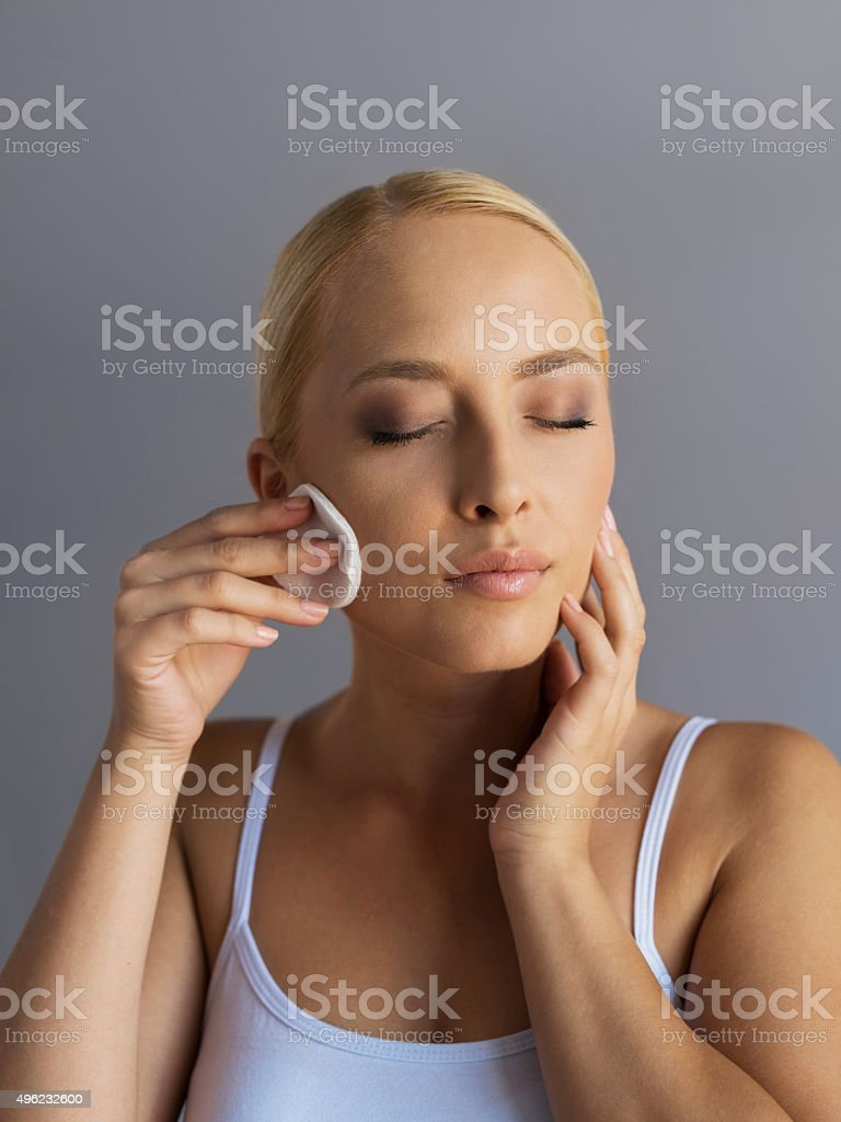 Woman using cotton swab for removing make-up from her skin. stock photo