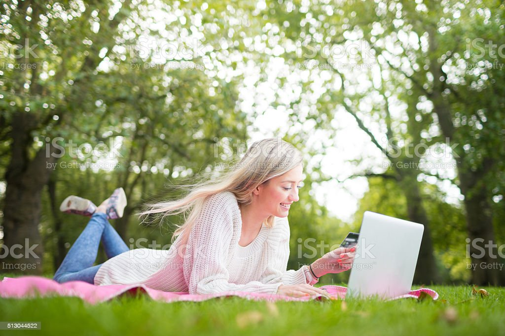 Woman using credit card shopping online with a laptop stock photo