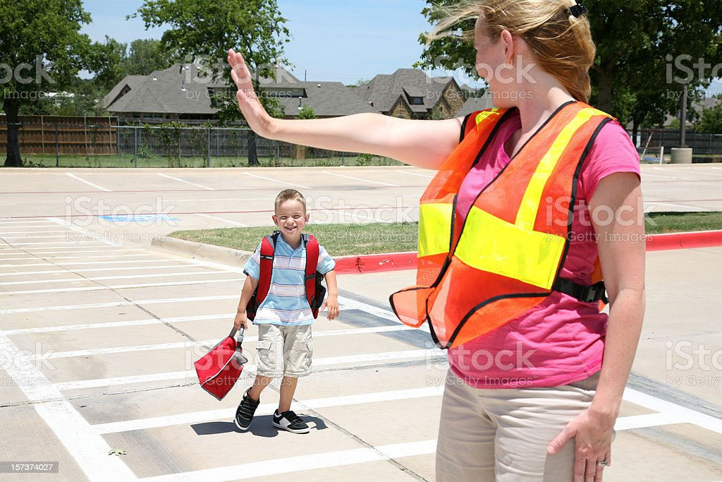 Woman Using Crosswalk Signals As Boy Crosses A Street stock photo