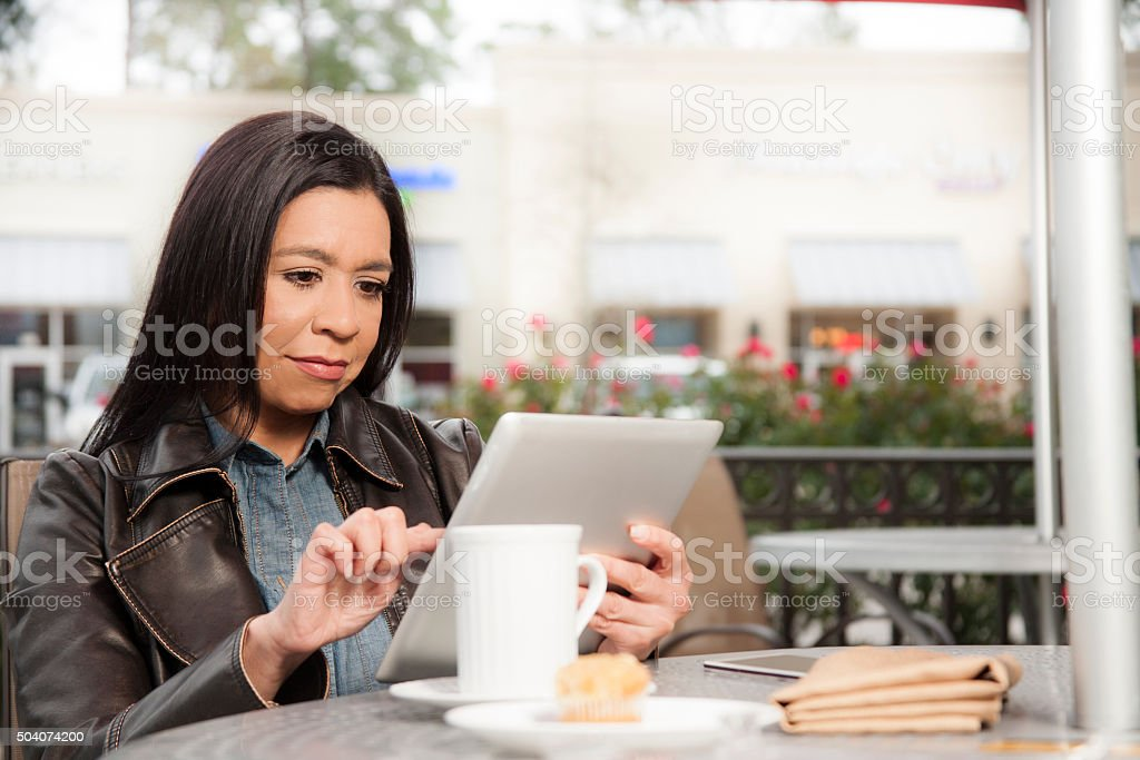 Woman using digital tablet at outdoor coffee shop. stock photo