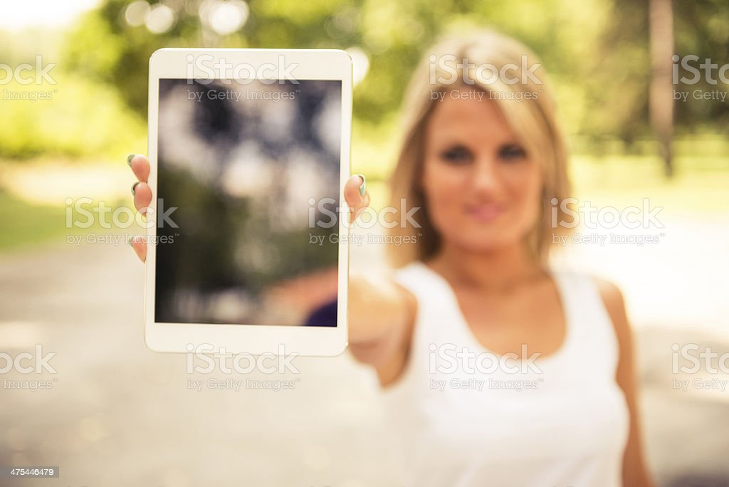 Woman using digital tablet at the park royalty-free stock photo