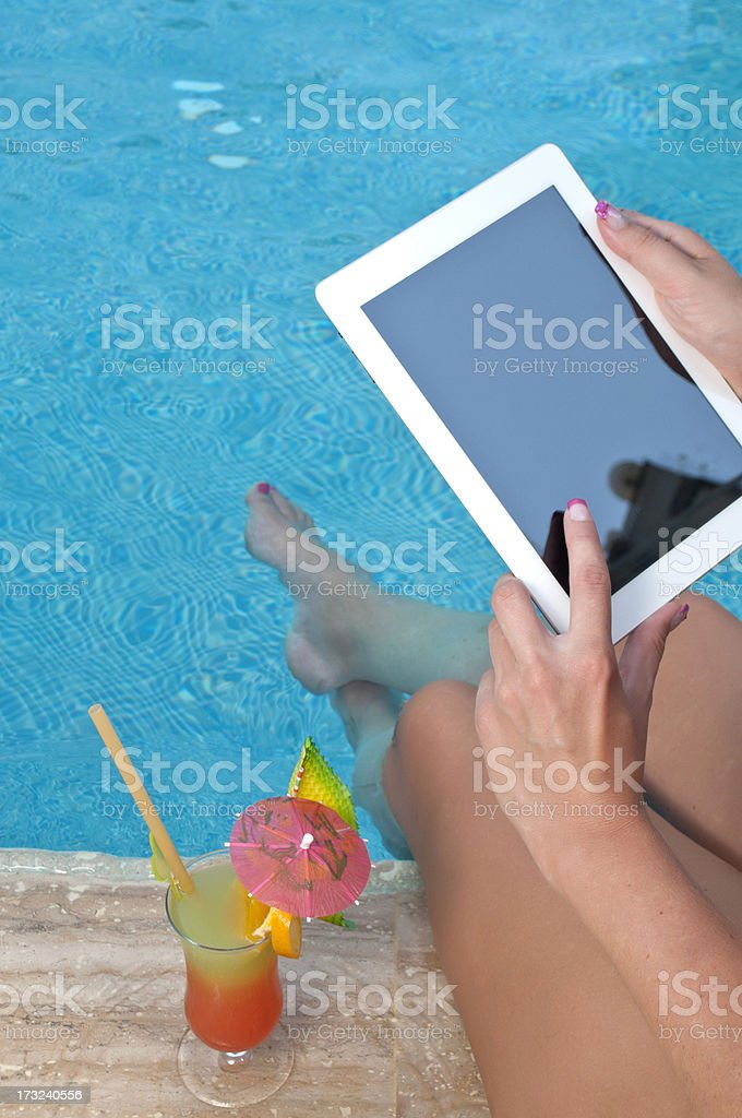 Woman using digital tablet by the pool royalty-free stock photo