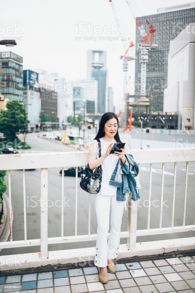 Woman using digital tablet on street stock photo