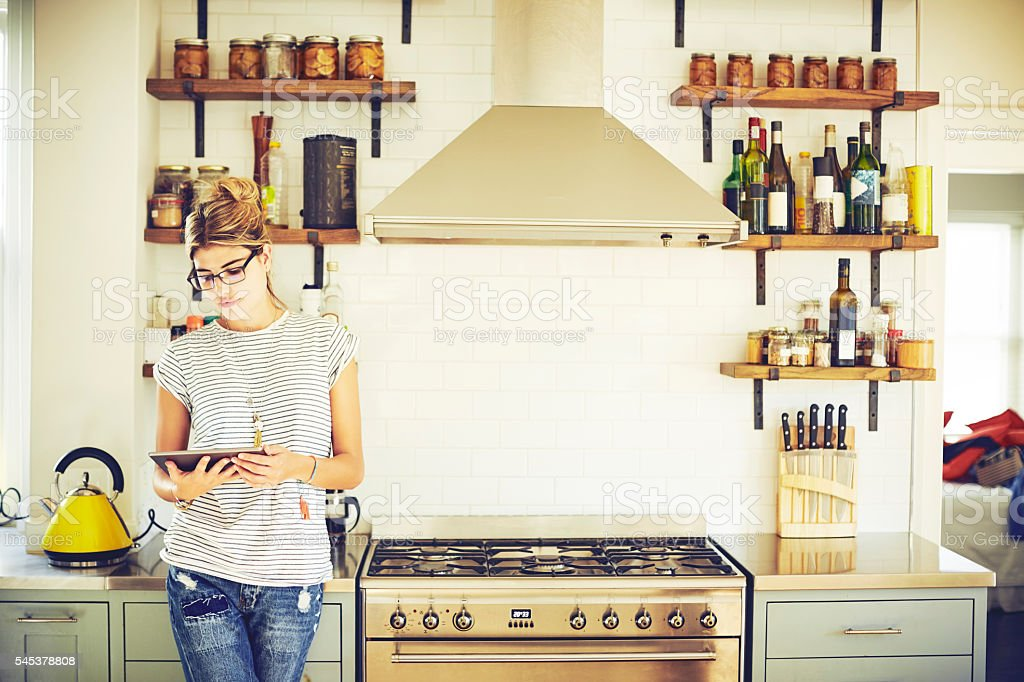 Woman using digital tablet while standing in kitchen stock photo