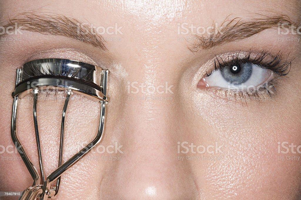 Woman using eyelash curlers stock photo