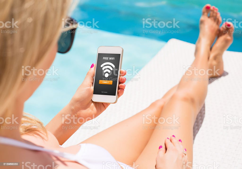 Woman using free wifi access on smartphone stock photo