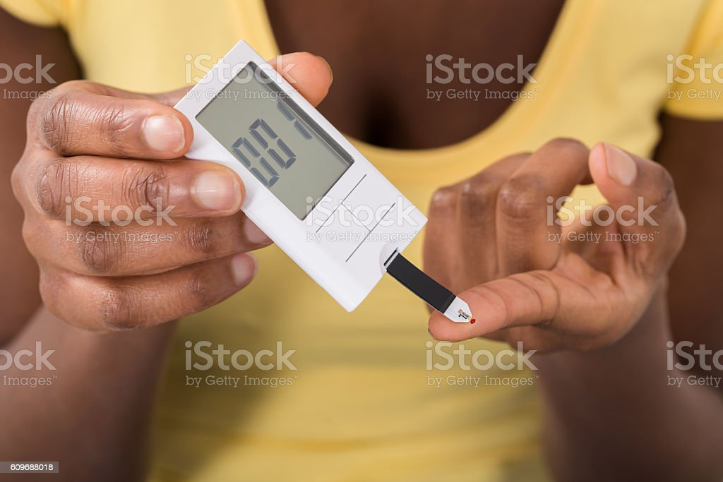 Woman Using Glucometer To Check Blood Sugar Level stock photo