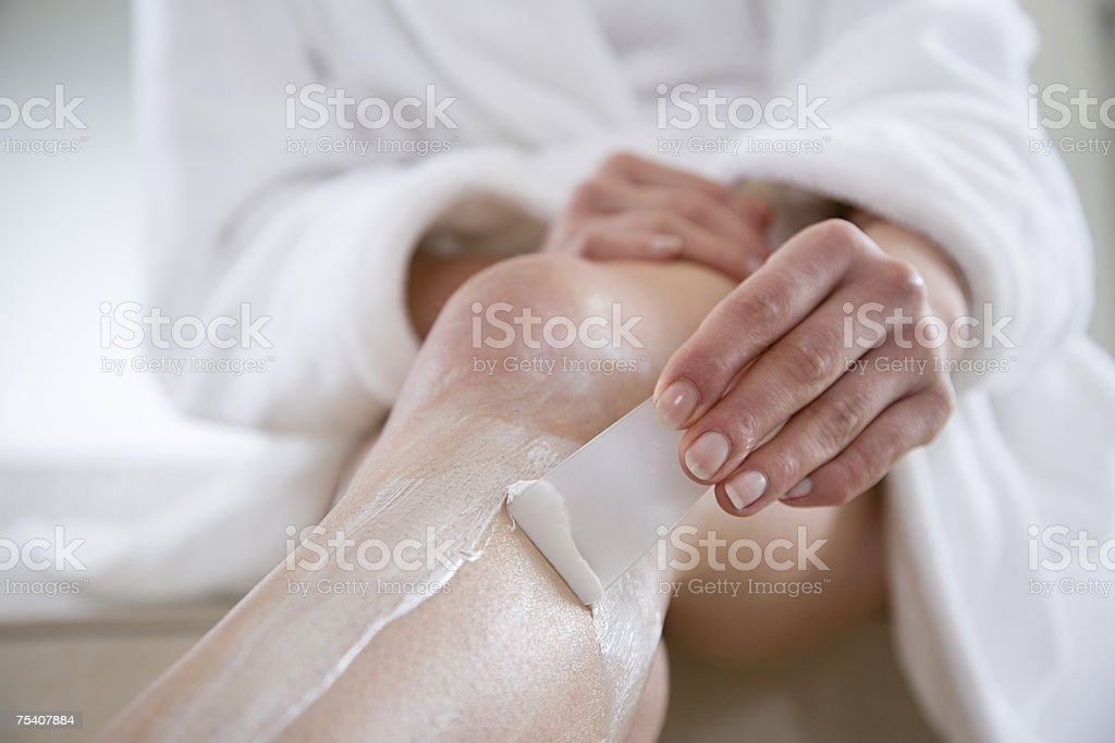 Woman using hair removal cream stock photo
