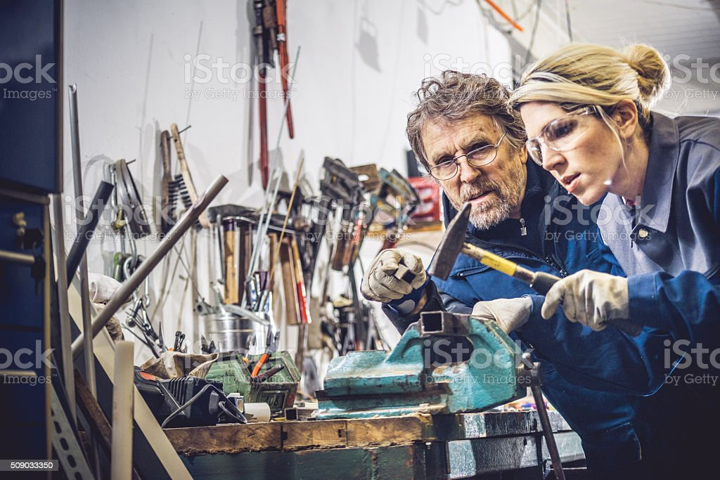 Woman Using Hammer in Mechanical Workshop stock photo