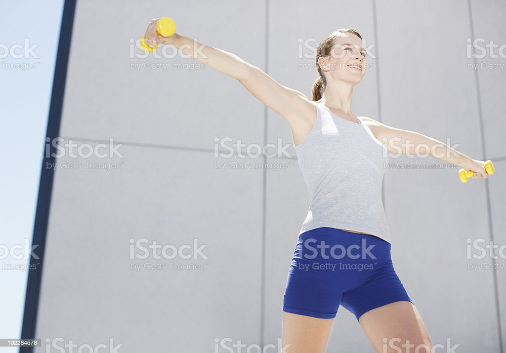 Woman using hand weights outdoors royalty-free stock photo