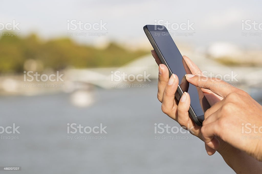 Woman using her cell phone, background Paris stock photo