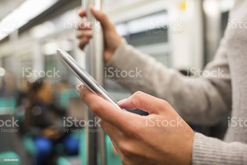 Woman using her cell phone in Subway stock photo