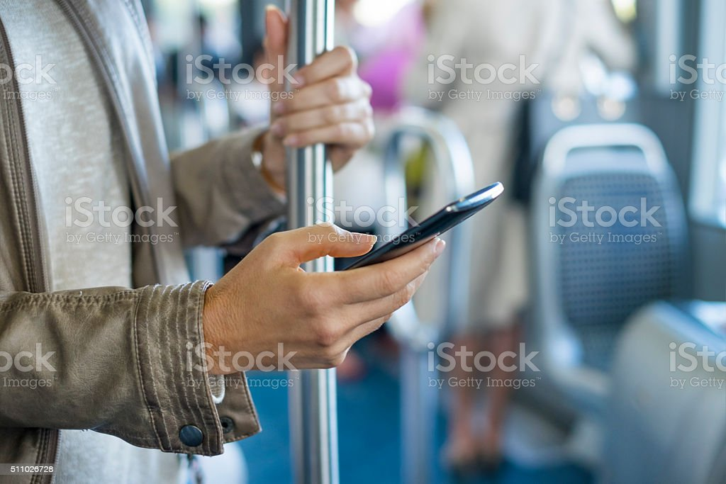 Woman using her cell phone on bus. Tramway. Sms, message stock photo