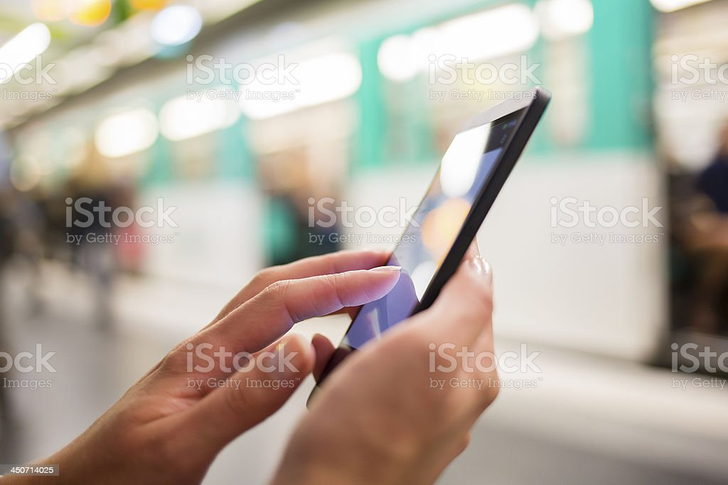 Woman using her cell phone on subway platform stock photo