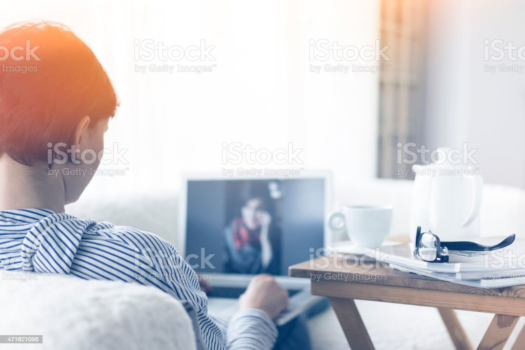 A woman using her laptop at home  stock photo
