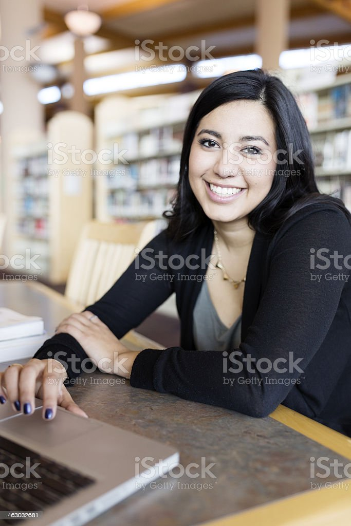 A woman using her laptop in a library setting stock photo