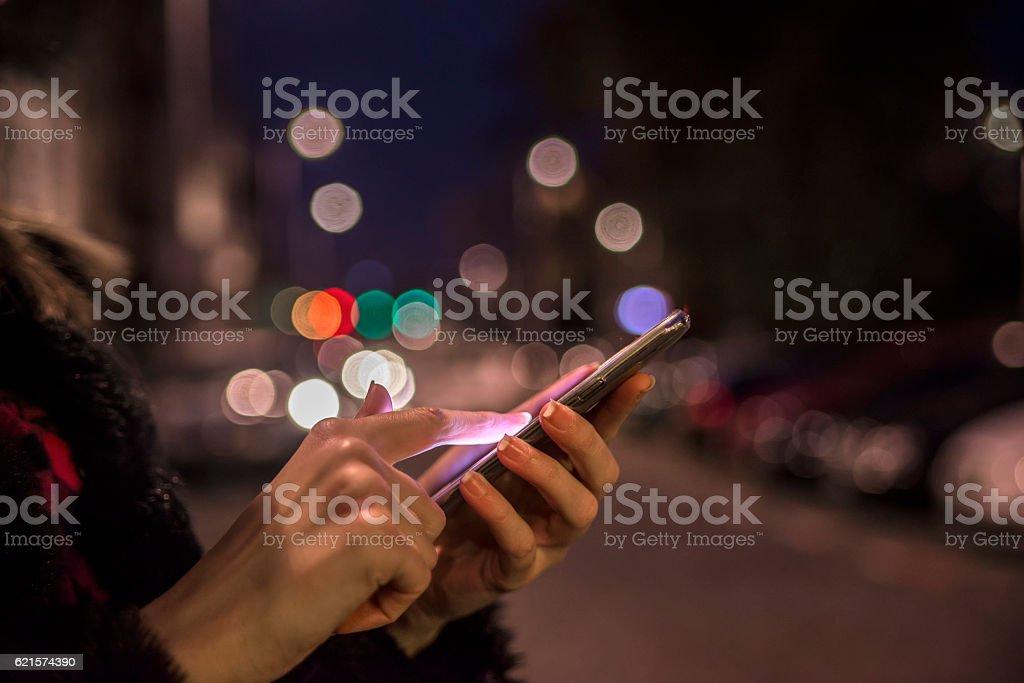 Woman using her mobile phone, city skyline night light backgroun stock photo
