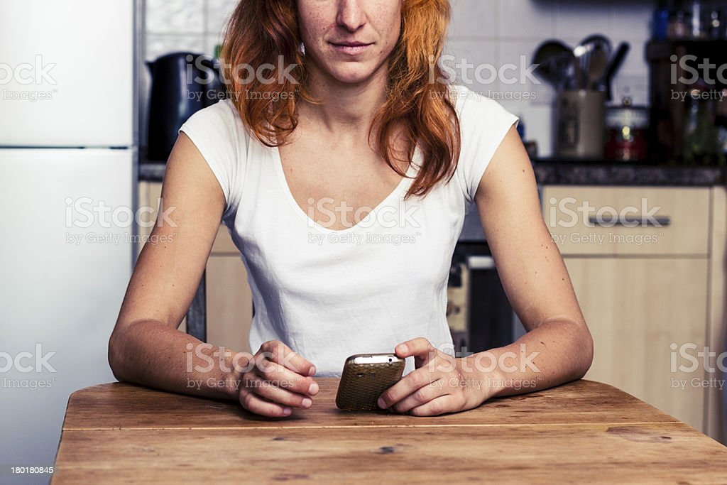 Woman using her phone in the kitchen royalty-free stock photo