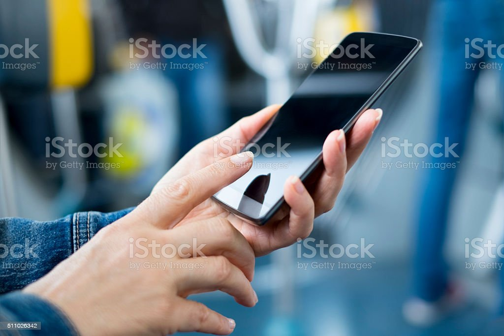 Woman using her smartphone on bus. Sms, message, app stock photo
