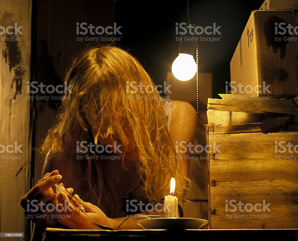 Woman Using Heroin in Grungy Room royalty-free stock photo