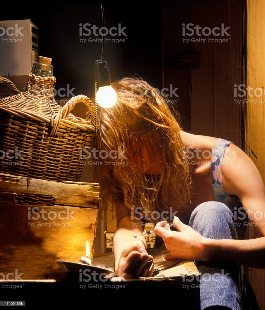 Woman Using Heroin in Grungy Room stock photo