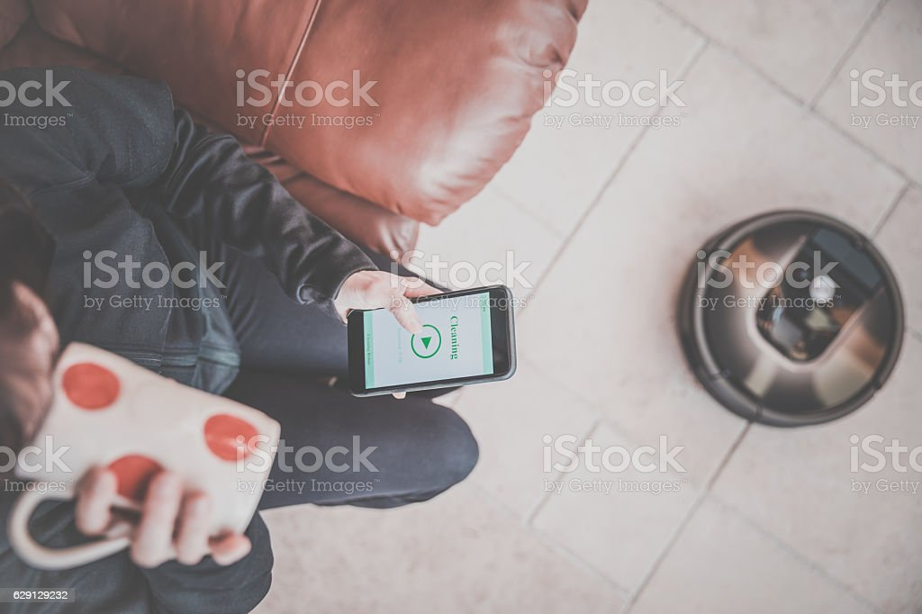 Woman Using Home Robot Cleaning App stock photo