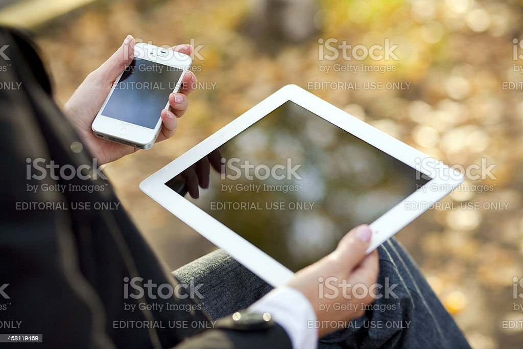 Woman using iPad and iPhone royalty-free stock photo