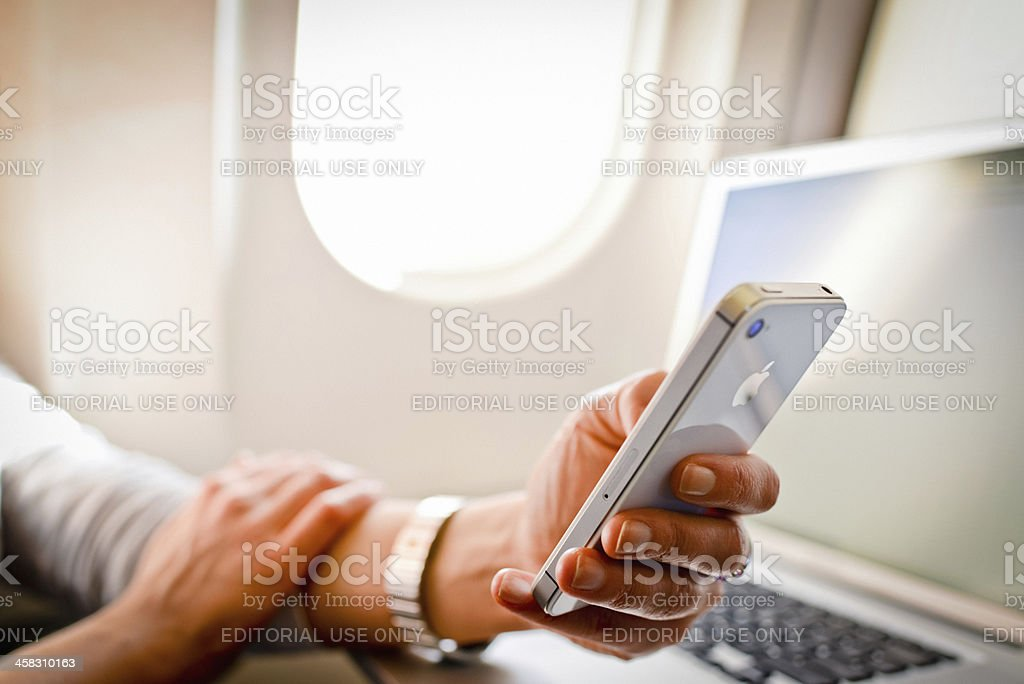 Woman using iPhone 4s and laptop in airplane during flight stock photo