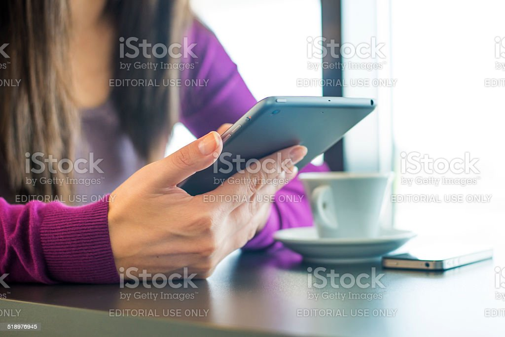 Woman using iPhone and iPad Mini stock photo