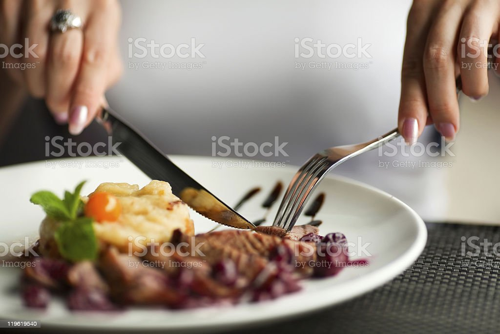 Woman using knife and fork to cut her dinner stock photo