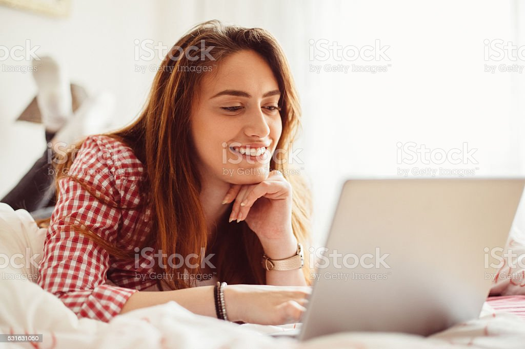 Woman using lap top in bed stock photo