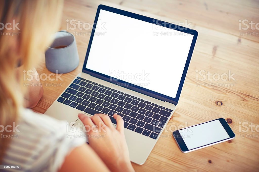 Woman using laptop and smartphone with blank screen at table stock photo