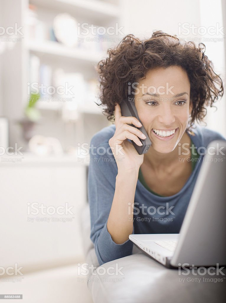Woman using laptop and talking on telephone stock photo