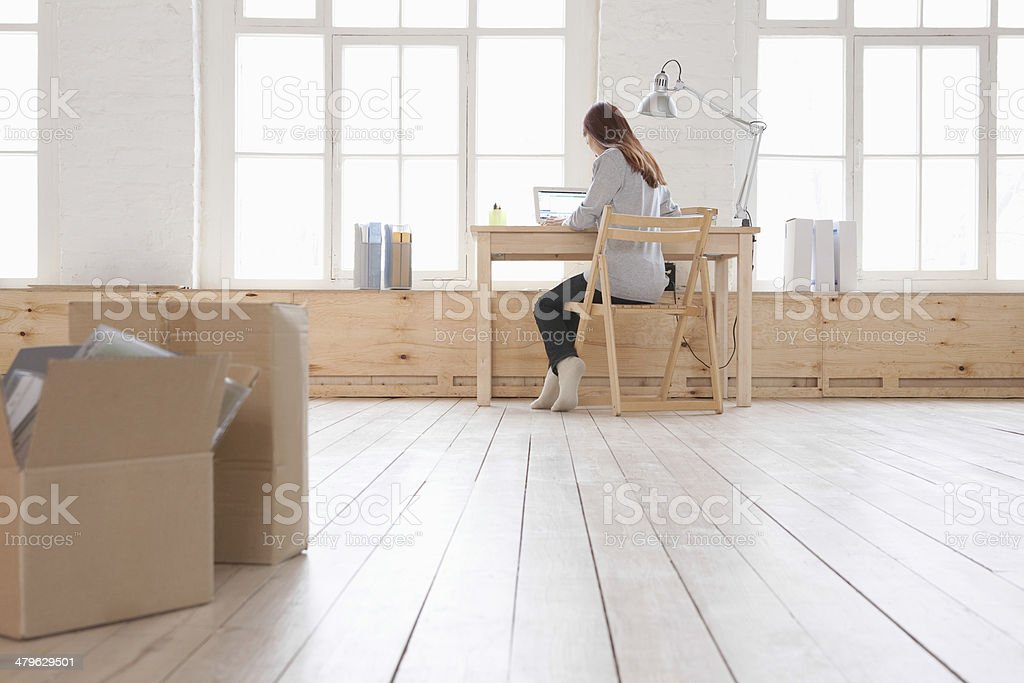 Woman Using Laptop At Desk In Loft Apartment stock photo