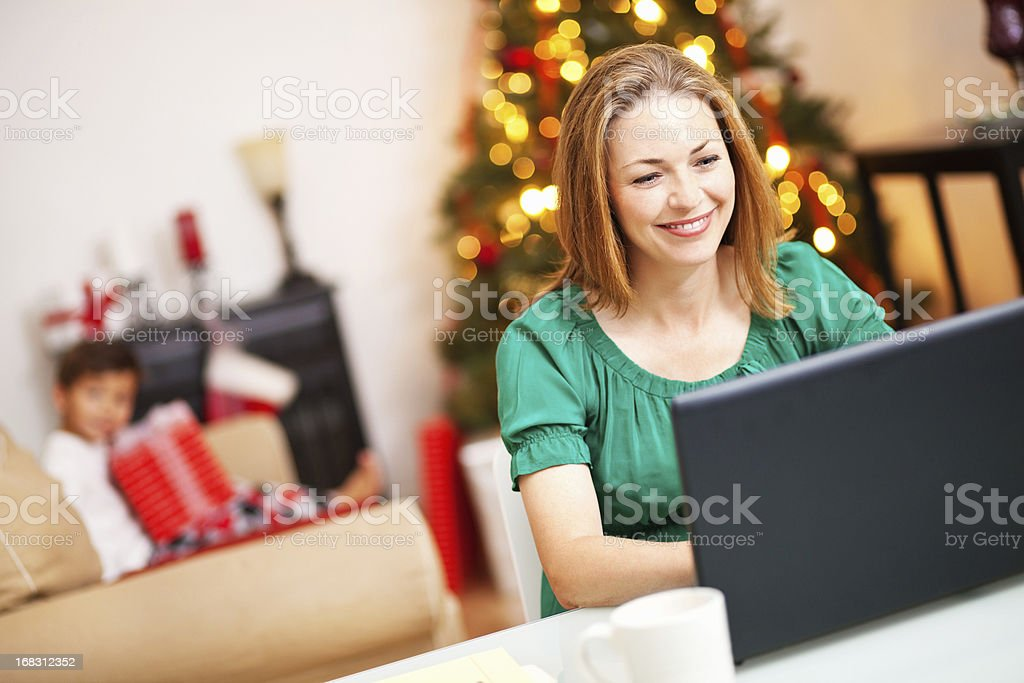 Woman Using Laptop at Home During Christmas Time royalty-free stock photo