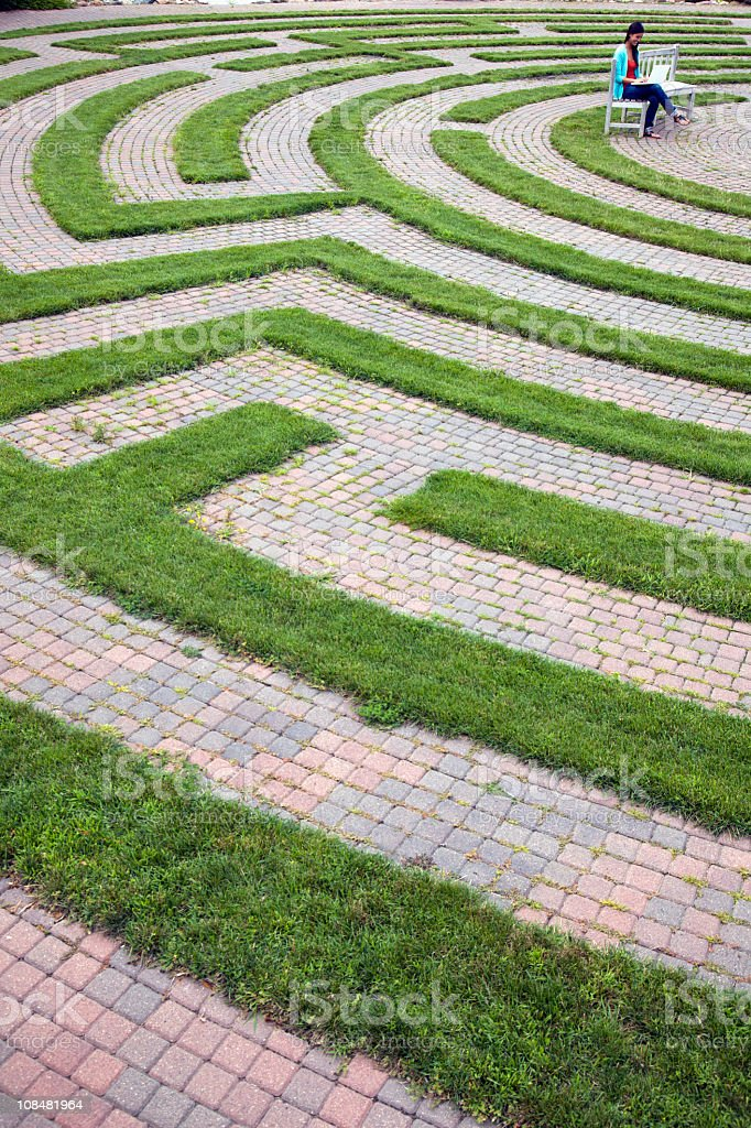Woman Using Laptop in a Cobblestone Maze royalty-free stock photo