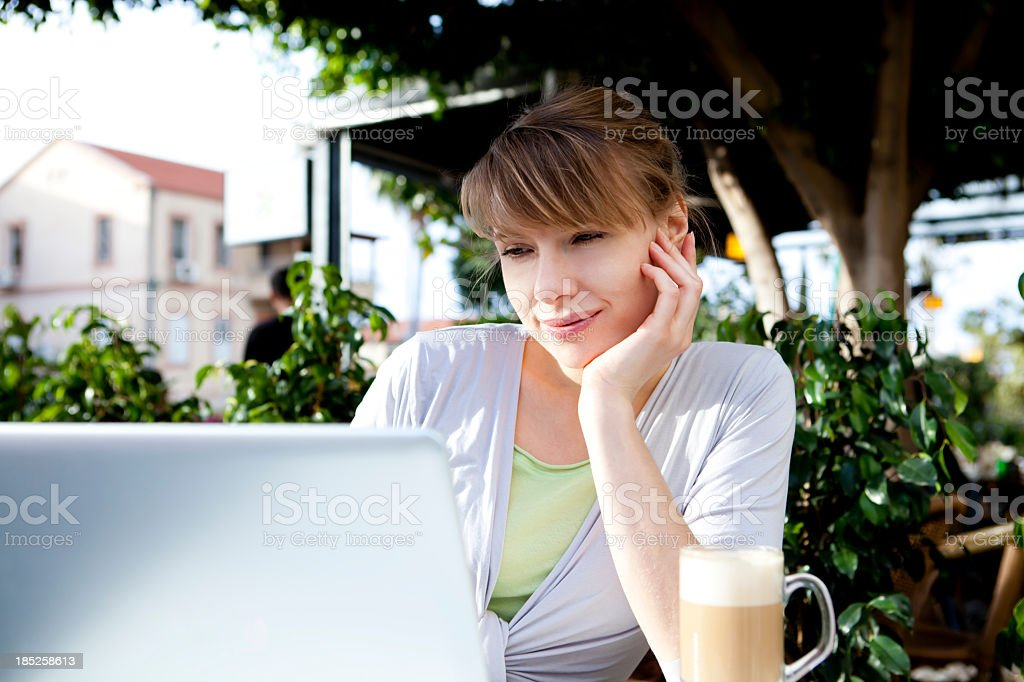 Woman Using Laptop In Cafe royalty-free stock photo