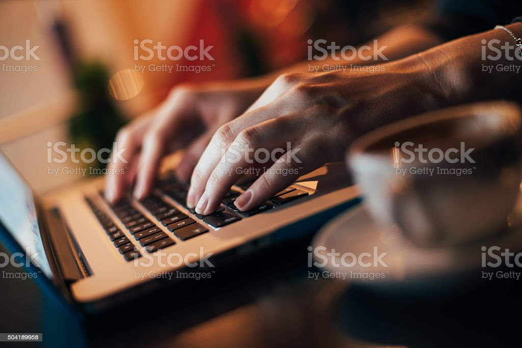 Woman using laptop in coffee shop stock photo