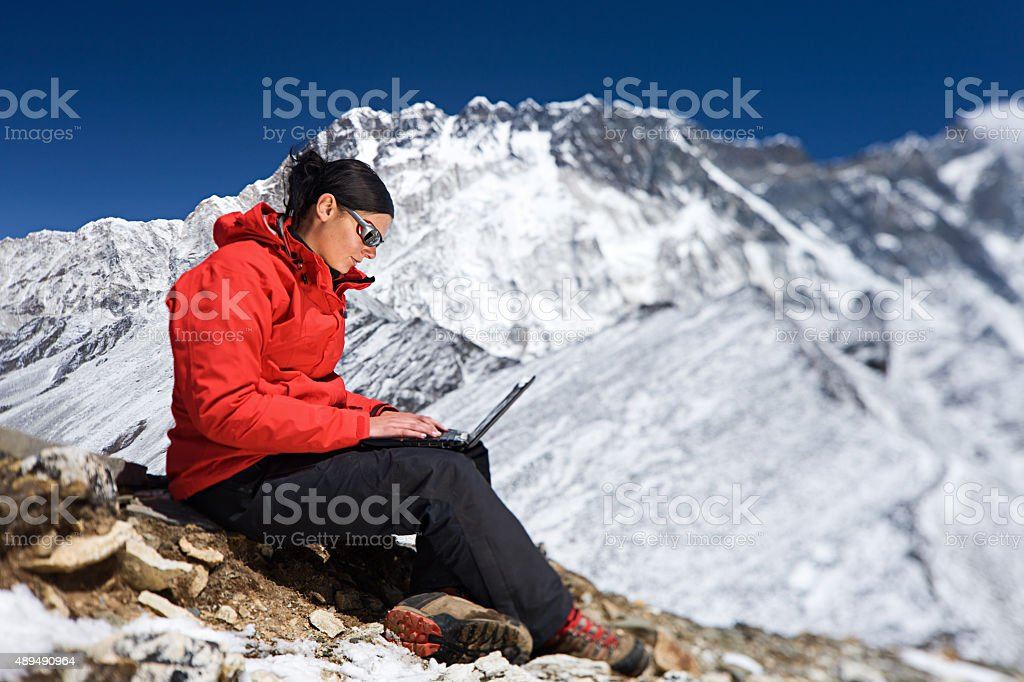 Woman using laptop in Mount Everest National Park, Nepal stock photo