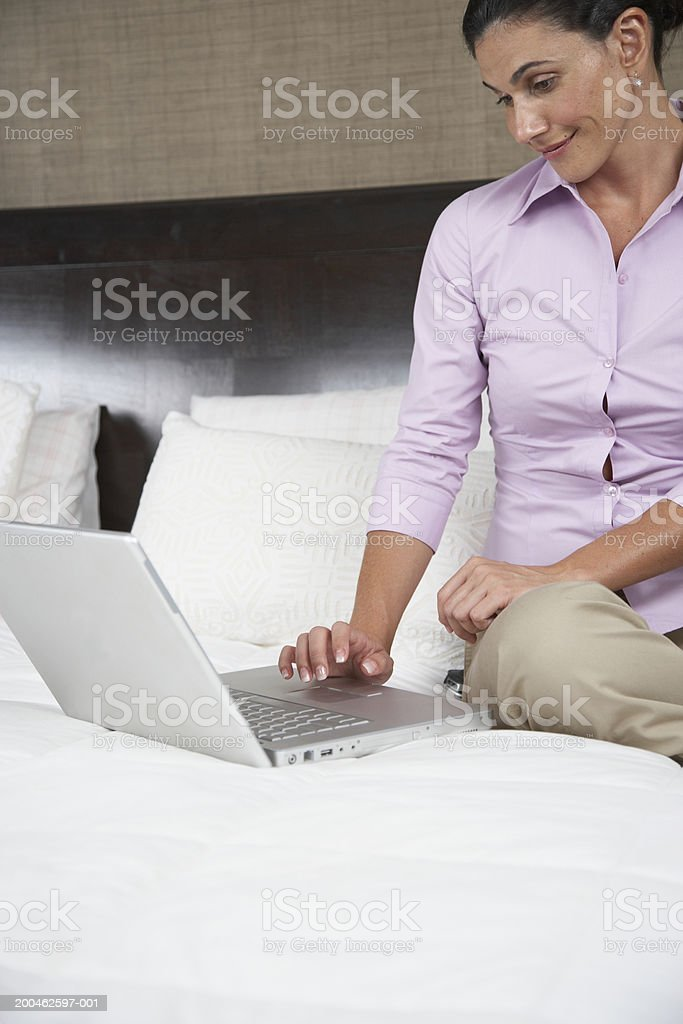 Woman using laptop on bed royalty-free stock photo