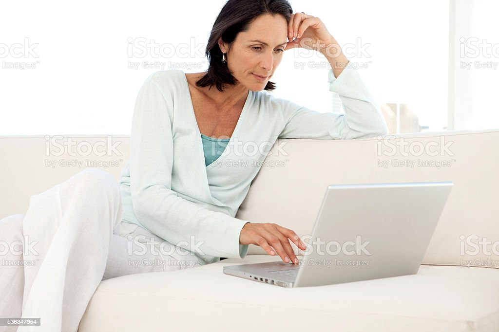 Woman using laptop on sofa stock photo