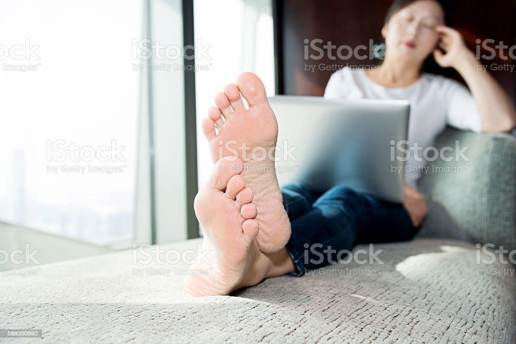 Woman using laptop on sofa stock photo