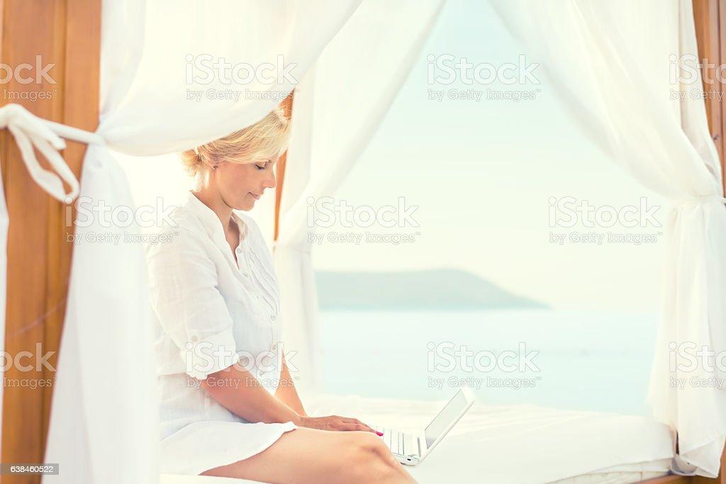Woman using laptop on the beach stock photo