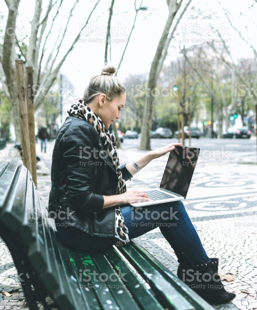 Woman using laptop on the street stock photo
