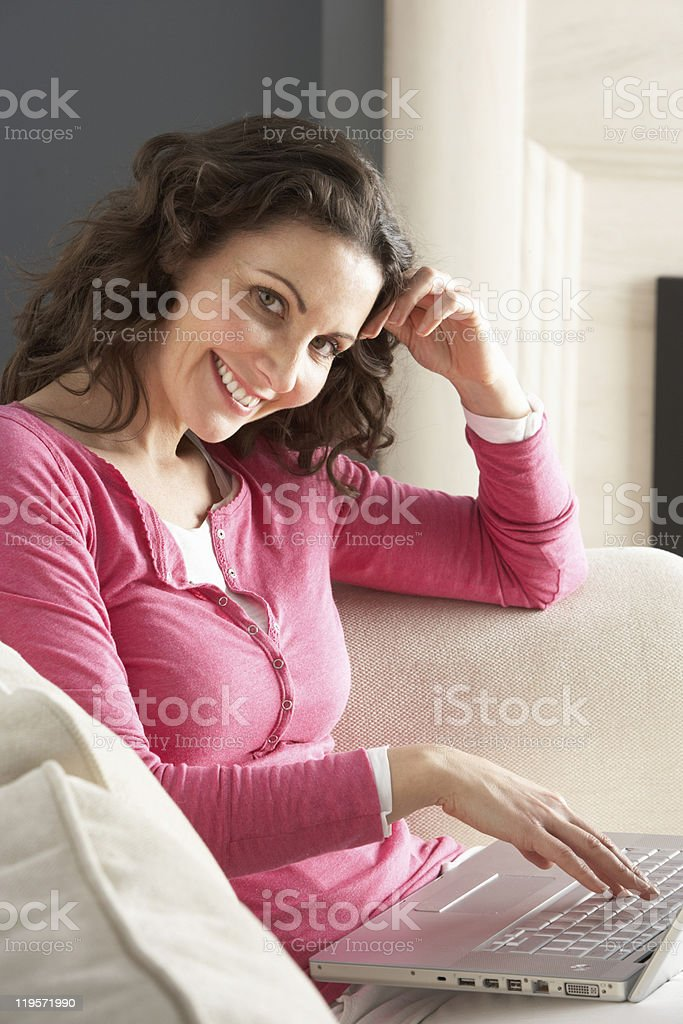 Woman Using Laptop Relaxing Sitting On Sofa At Home royalty-free stock photo