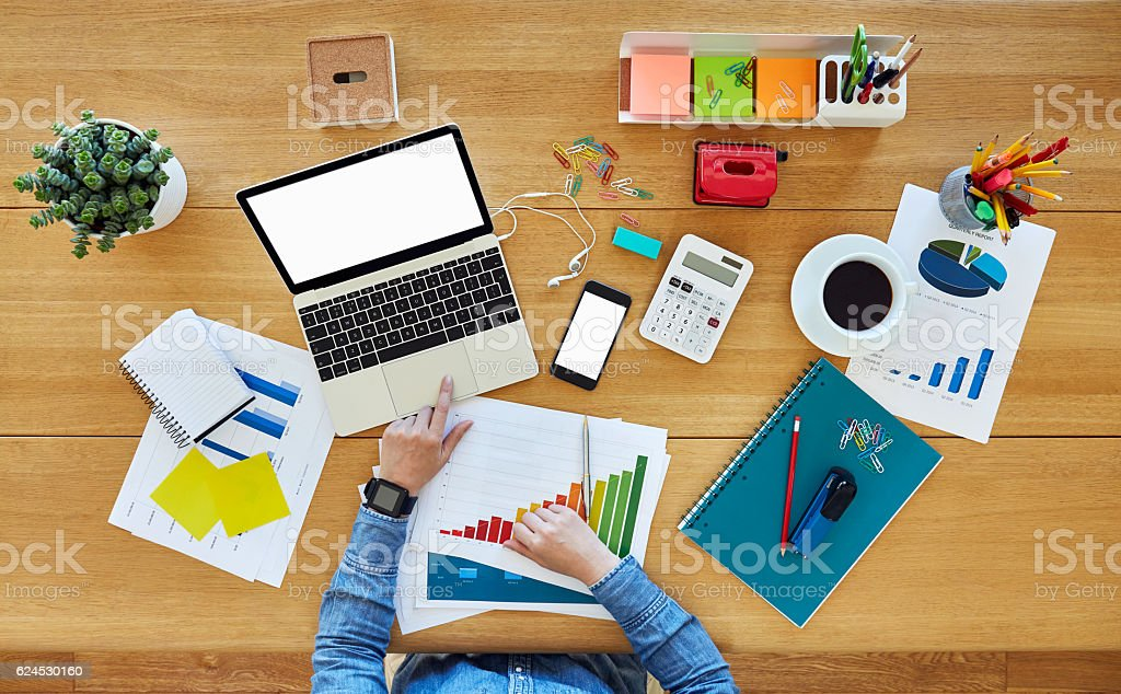Woman using laptop surrounded by graphs and office supplies stock photo
